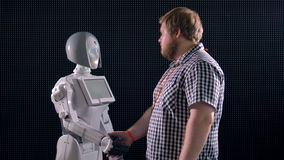 En handskakning mellan en man och en robot stock video
