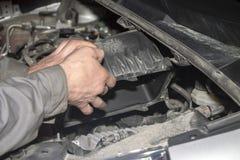 En handtekniker som kontrollerar eller fixar motorn av en modern bil Utbyte av luftfiltret royaltyfri foto