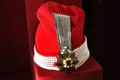 En hatt med juvlar på en röd bakgrund arkivfoto