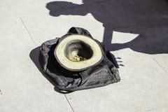 En hatt med mynt ligger på asfalten i skuggan av en gatagitarrist royaltyfri fotografi