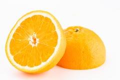 En hel apelsin som klipps i halva Arkivfoton