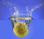 En hel citron som plaskar in i vatten Royaltyfri Bild