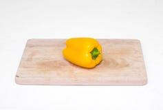 En hel gul spansk peppar på en skärbräda Arkivfoto