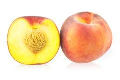 En hel persika och halvan persika Arkivfoto
