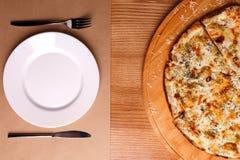 En hel pizza tjänas som på tabellen arkivfoton