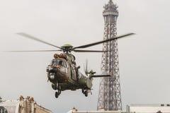 En helikopter framme av Eiffeltorn för Bastilledagen i Paris - FN-hélicoptère häller le 14 Juillet àParis Royaltyfri Fotografi