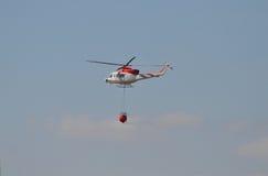 En helikopter som tar vatten till en Bush brand Royaltyfri Foto