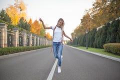 En hellång stående av en härlig blondin, som dansar i mitt av en väg i ett stort, parkerar Händer lyftte till sidan fotografering för bildbyråer