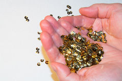 En hembra da las lentejuelas de oro para el bordado en el fondo blanco Fotos de archivo libres de regalías