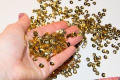En hembra da las lentejuelas de oro para el bordado en el fondo blanco Imágenes de archivo libres de regalías