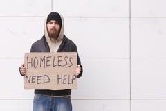 En hemlös man är den stående yttersidan i ett kallt väder med ett papptecken som frågar för hjälp utomhus- Arkivbild