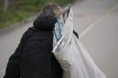 En hemlös man går med en påse arkivbild