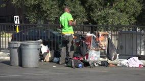 En hemlös man som sorterar flaskor som han har samlat på den återanvändande mitten arkivfilmer