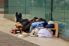 En hemlös sover i en centrumgata arkivbild
