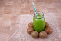 En hemlagad kiwismoothie för strikt vegetarianfrukost på ett vitt tyg och på en träbakgrund Healthful ingredienser royaltyfria foton