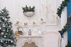 En hemtrevlig vardagsrum som tänds med talrika ljus dekorerat klart att fira jul Jul hyr rum inredesign arkivfoto