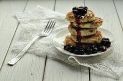 En hög av stekte ostpannkakor, en gaffel på en vit linneservett, ett exponeringsglas av mjölkar, secveral ägg och en platta med m Royaltyfri Foto