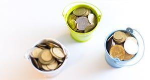 En hink med mynt på en vit bakgrund är isolaten äganderätt för home tangent för affärsidé som guld- ner skyen till Arkivbild