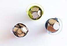En hink med mynt på en vit bakgrund är isolaten äganderätt för home tangent för affärsidé som guld- ner skyen till Fotografering för Bildbyråer