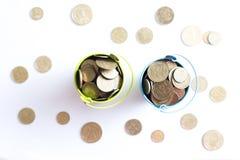 En hink med mynt på en vit bakgrund är isolaten äganderätt för home tangent för affärsidé som guld- ner skyen till Arkivbilder