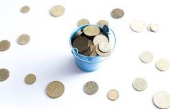 En hink med mynt på en vit bakgrund är isolaten äganderätt för home tangent för affärsidé som guld- ner skyen till Royaltyfri Foto