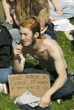 En hippy har att ge fred en möjlighetsslogan på hans protesttecken på en marsch för anti--Irak krigprotest i Santa Barbara, Kalif royaltyfri foto