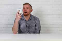 En hipsteraffärsman talar på telefonen Han är mycket emotionell På en vit bakgrund isolerat Affärsman som talar på pet royaltyfria bilder