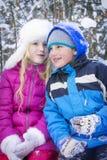 En hiver, le garçon couvert de neige de forêt avec l'entretien blond de fille Image libre de droits