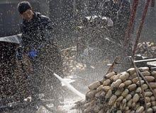 En hiver les travailleurs gagnent leur monnaie métallique dans l'étang Images stock