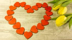 En hjärta i rött med en tulpanbukett arkivbilder