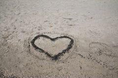 En hjärta i sanden på en strand Fotografering för Bildbyråer