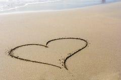 En hjärta i sanden på en härlig strand i solskenet med utrymme för vidare att redigera arkivbilder