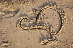 En hjärta i sanden på solnedgång Arkivbilder