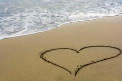 En hjärta i sanden på en strand med fritt utrymme för text arkivfoto