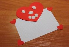 En hjärta med en framsida som göras av skal som ligger på ett blad av ett block på kanten av arkhjärtorna Royaltyfria Bilder