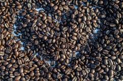 En hjärta och kaffebönor Arkivfoton