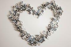 En hjärta som fodras med en variation av muttrar, bultar, skruvar och packningar med den tomma utrymmeinsidan på ett ljust - grå  royaltyfri bild