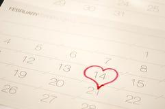 En hjärta som omger Februari 14 på kalendern Arkivbild