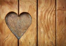 En hjärtaform sned i det wood slutet för tappning upp Royaltyfri Fotografi