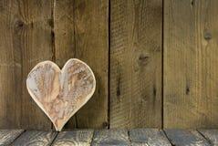 En hjärta av trä på en gammal lantlig bakgrund för ett hälsningkort. Royaltyfri Foto