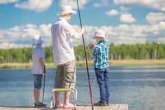 En hobby för man` s - en fader med hans söner på fiske i bra weathe Royaltyfri Bild