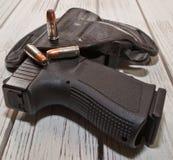 En holstered svart pistol med flera kulor på en trätabell Arkivbild