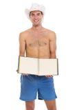 En hombre de las vacaciones en el sombrero de la playa que muestra el phot en blanco Imagen de archivo