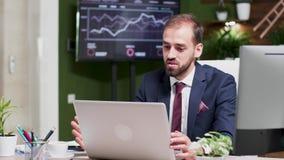 En hombre de negocios joven de mirada moderno, creativo de la oficina de negocios está teniendo una llamada video metrajes