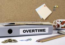 En horas extras - carpeta en el escritorio de oficina blanco imagen de archivo