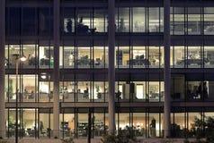 En horas extras en un edificio de oficinas moderno Fotos de archivo