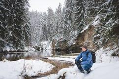 En huka sig ned fotvandrare vid vinterfloden arkivbild