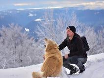 En hund och hans ägare som spelar med snö Royaltyfria Foton