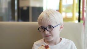 En hungrig pojke äter ivrigt pizzamargaritan lager videofilmer