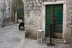 En husdörr med en stol och en tabell på en gata royaltyfri bild